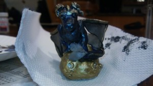 blue, gold, and black dragon on a pile of treasure.